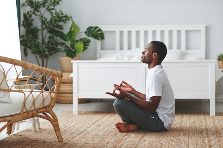 Young Black man sitting cross-legged, meditating.
