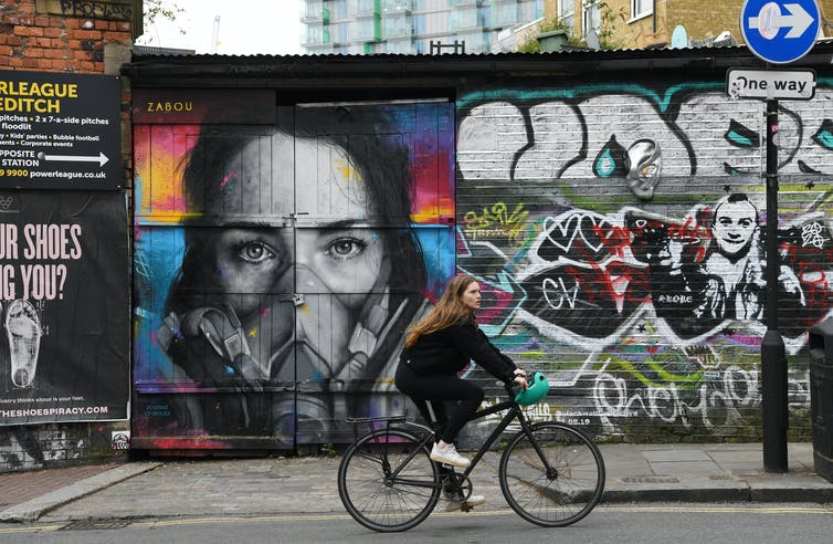 Woman cycles past street art of person wearing respirator.
